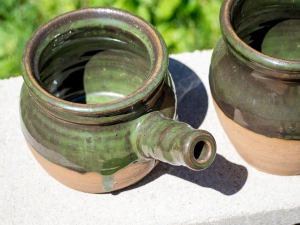 Green ceramic bowl with cylindrical handle.