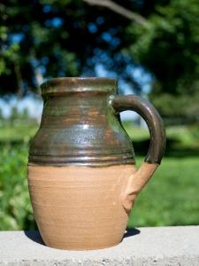 Medium sized ceramic water pitcher. Green glaze on top half. Unglazed bottom half.